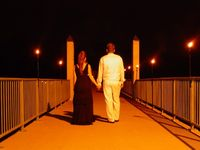 Diana and Kyle walk across the bridge at night